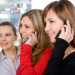 Foto Stock: Three girls talking by mobile phones