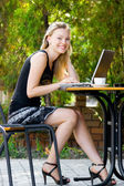 Happy beautiful mode in cafe with laptop — Stock Photo