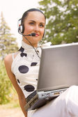 Beautiful woman with laptop and headset — Stock Photo