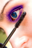 Beautiful woman applying mascara on her eye with brush — Stock Photo