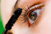 Beautiful woman applying mascara on her eye with brush — Stok fotoğraf