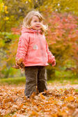 Little blond girl in autumn park — Stockfoto