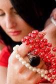 Pretty brunette holding red and white beads in hand — Stock Photo
