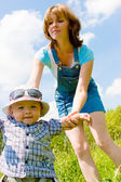 Happy mother holding son's hand — Stock Photo