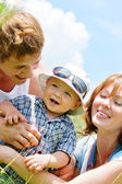Happy family with son over blue sky background — Stock Photo