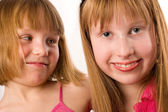 Two beautiful little smiling girls looking sisters isolated on w — Stock fotografie