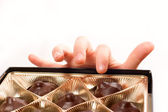 Child's hand picking chocolate candy from box isolated over whit — Стоковое фото