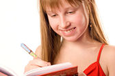Pretty teenager girl smiling, writing down to notepad isolated o — 图库照片