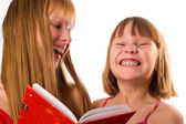 Two little girls looking like sisters holding red book, laughing — Stok fotoğraf