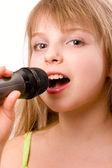 Litle ładna dziewczyna śpiewa w mikrofon na białym tle nad białym — Zdjęcie stockowe