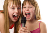 Two cute girls, 9 and 12 years age singing to microphone, isolat — Стоковое фото