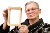 Old man holding empty wooden frame — Stock Photo