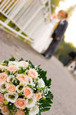 Bride and groom with flowers in front — Stok fotoğraf