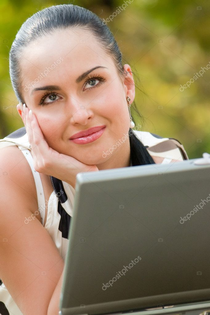 Happy young woman with laptop outdoors shot  Stock Photo #10166234