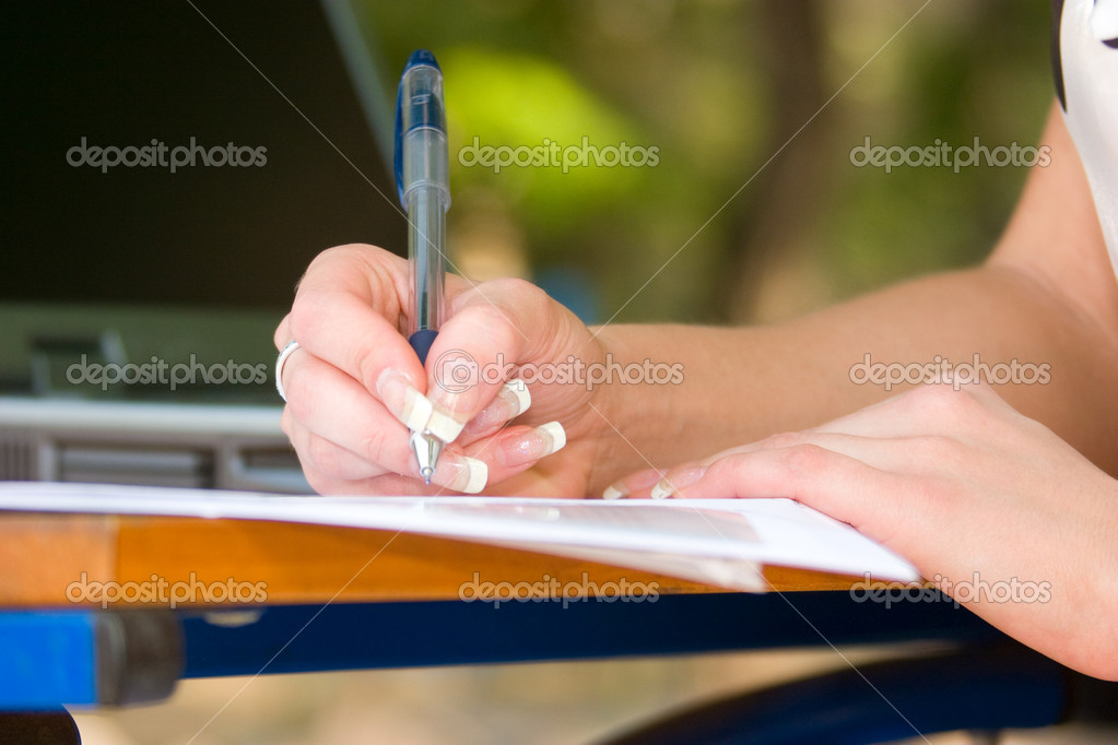 Woman's hand with pen writing down notes with laptop on background — Stock Photo #10166269