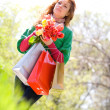 Beautiful woman with shopping bags and tulips — Stock Photo
