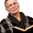 Stock Photo: Elderly man reading a book