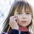 Adorable little girl talking by cellphone — Stock Photo