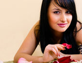 Pretty brunette woman with rose petals — ストック写真