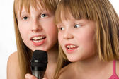 Two little sisters singing in microphone — 图库照片