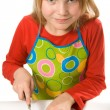 Little girl wearing apron slicing mushrooms — Photo