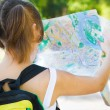 Smiling girl with backpack holding city map — Stockfoto
