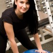 Young brunette in gym with exercise ball — Stock Photo