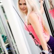 Pretty blond woman exercising on pulldown station — Stock Photo