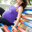 Pregnant woman sitting on park bench — Stock Photo