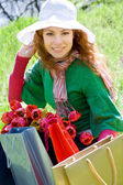 Bella mujer con bolsas de compras y tulipanes — Foto de Stock