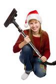 Usmívající se dospívající dívka v santa hat s vysavačem koště — Stock fotografie