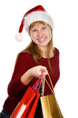 Teenager girl in christmas hat with shopping bags — Stock Photo
