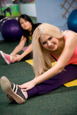 Young women stretching on gym floor — Stock Photo