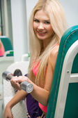 Young smiling woman with a dumbbell — Foto de Stock