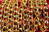 Goldene farbe kette über roter seide — Stockfoto