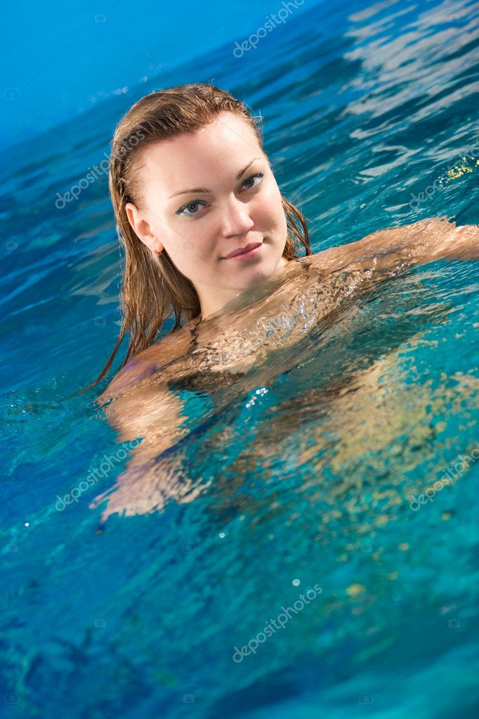 Beautiful young woman relaxing in indoor pool  Stock Photo #10185356