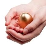 Hands holding golden egg — Stock Photo