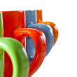 Multicolored ceramic mugs over white — Stock Photo