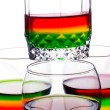 Glasses filled with rainbow coloured alcohol - Stock Photo