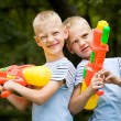 Two smiling twin brothers with water guns — Стоковая фотография