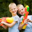 Stock Photo: Two smiling twin brothers with water guns