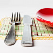 Red plate, knife and fork isolated on white — Stok fotoğraf