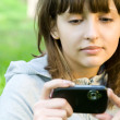 Young woman taking picture with digital camera — Stock Photo #10370730