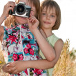 Two little girls taking picture with SLR camera - Stock Photo