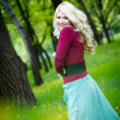 Smiling blond girl over green grass — Stock fotografie