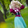 Smiling blond girl over green grass — Foto Stock