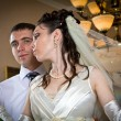 Beautiful young bride kissing groom in indoor setting — Stock Photo