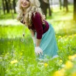 Smiling blond girl over green grass — Stock Photo #10370832