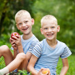 Two smiling twin brothers holding fruits — Stock fotografie