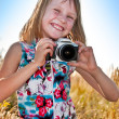 Little girl taking picture with SLR camera — Stock fotografie